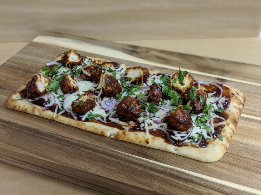 Steamy and crisp BBQ Chicken flatbread on a wooden platter.