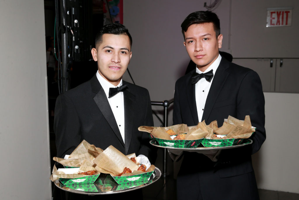 Servers holding trays of Wingstop at Brandon Maxwell's NYFW show.