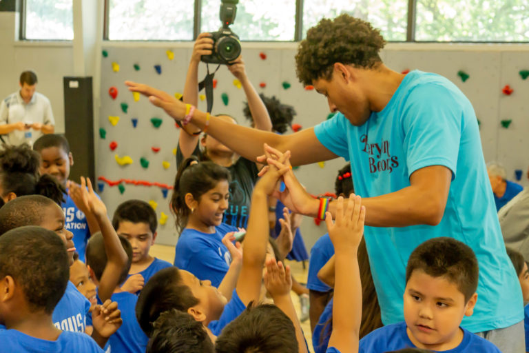 Dallas Mavs player Justin Jackson coaches the children for a basketball clinic